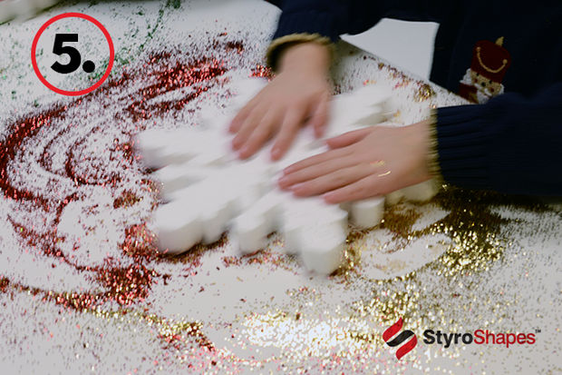 A child finishes covering his Styrofoam snowflake in glitter.